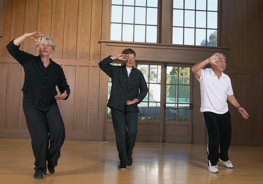 Three seniors practicing Tai Chi indoors